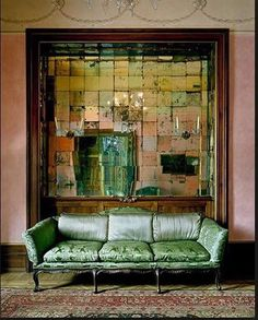 old mirror tiles, pink walls and a wonderful green sofa