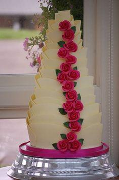 White Belgian chocolate finished cake with cascading sugar roses.