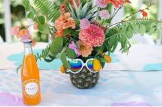 A colorful floral centerpiece in a pineapple vase ideal for a summer wedding celebration.   Verbena