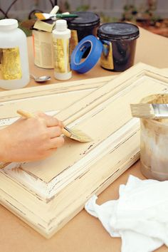 Step 7: Distress the cabinets by chipping back corners. Use steel wool to rub the areas covered with wax or petroleum jelly to allow stain to show through.Step 8: Ap