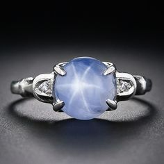 Petite platinum and diamond ring, circa 1930, features a shimmering light pastel blue star sapphire