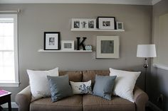 Love these shelves, initial and frames. Great living room wall idea :)
