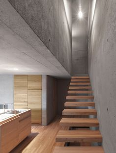 Wooden staircase steps + concrete walls. Haus Rüscher by OLKRÜF | thelayer
