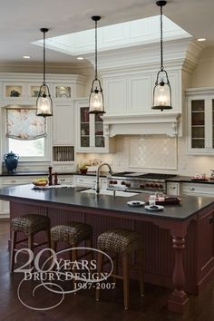 A Trio Of Corsica Pendants Illuminate An Extra Long Kitchen Island - Lights on top of kitchen island