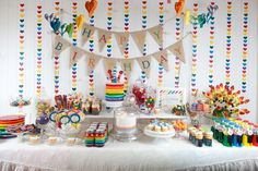 Rainbow Party Dessert Table - the rainbow garland backdrop makes such an impact! #kidsparty