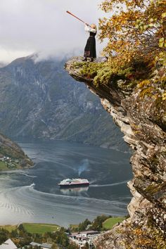 Woman in bunad (national costume) blowing in a wind instrument on a place called Flydalsjuvet in Geiranger in Møre & Romsdal county, Norway http://naroyfjorden.no/ - From THE ESSENCE OF THE GOOD LIFE™     http://www.pinterest.com/ConceptDesigner/   https://www.facebook.com/pages/The-Essence-of-the-Good-Life/367136923392157