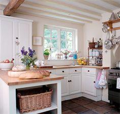 White cabinets, wood worktops. Range cooker. Love the pan shelf over the range.