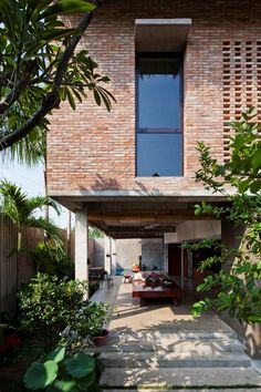 Ventilation holes in the brick facade and a roof covered in palm leaves are among the methods used to improve the climate inside this Ho Chi Minh City house Post Modern Architecture, Architecture Résidentielle, Tropical Architecture, Brick Facade, Facade House, Modern Exterior, Exterior Design, House On Stilts, Brick Design