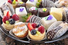 Mini Dessert Tray: Assortment of bite-sized éclairs, cream puffs, fruit tarts, petit fours, chocolate dipped strawberries, cannoli and brownie bites.