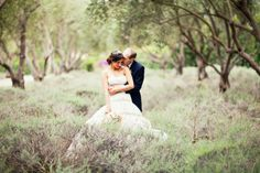 Groom behind, with hands wrapped around bride, bride with one arm on his and the other down holding bouquet