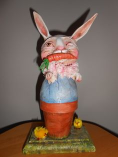 "POTTED BUNNY, 11"" tall.  2013, Original Debra Schoch piece. Holds carrot in both and has one eye closed.   Paper Clay Material."