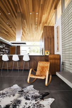 Hardwood ceiling, cowhide rug with concrete- interesting blend of modern and rustic