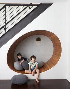 """Kids Room, Playroom Room Type, and Dark Hardwood Floor The space below the stairs was turned into a cheerful play area for the two boys. """"We built an egg shaped 'nook' underneath the staircase, and filled it with soft 'pebble' pillows,"""" adds Tang."""