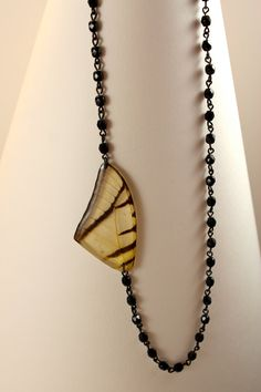 A(N)NA Offset Real Butterfly Wing with Jet on Niobium Chain. $45.00, via Etsy.