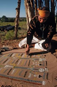Photograph:A Navajo shaman creates a sand painting. Such paintings serve religious—especially