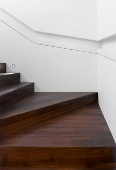 Stair Design Ideas - 9 Examples Of Built-In Handrails // This white wall that wraps around the stairs has a section cut-out of it to house the handrail.