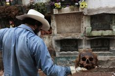 A grave cleaner holds up a skullm with thick hair still clinging to it, during exhumation works at the Cemetery General in Guatemala City May 24, 2013
