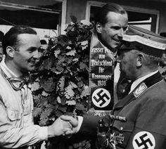 Gran Premio di Germania 1938. Il capo della motorizzazione tedesca, Adolf Huenlein, si congratula con Hermann Lang, 2° arrivato. Sul podio più alto, clamorosa affermazione del giovane inglese Richard Seaman su Mercedes. Huenlein sta già pensando a come dare la notizia a Hitler...