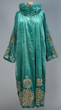 SEQUINED VELVET EVENING COAT, 1923. Turquoise silk having ruched and padded stand collar, decorated on sleeve and at hem with a stylized floral in platinum sequins and metallic cord embroidery,