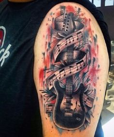 Electric guitar tattoo enveloped in melodic notes. The electric guitar seems to have feathers attached behind it and the background is a combination of red and blue inked splashed all over.