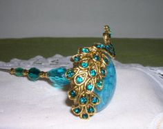 A hat pin with a blue peacock has shining gold and blue feathers laying across a blue agate