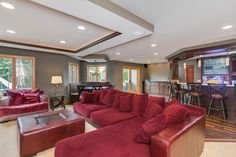 A striking red sectional and oversized, plush armchair boast of comfort and style in this transitional basement home theater. Designed for optimal entertaining, built-in cabinets and fireplace, a wet bar and additional table and seating are all framed within several different types of wood and stains to match the unique floor.