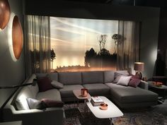 Dunkle Wände mit Leuchtschalen aus Kupfer, eine einladende Couch mit genug Platz zum entspannen. So gemütlich kann es zu Hause sein.