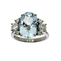 An aquamarine and diamond seven stone ring consisting of a principal aquamarine with diamonds either side all in palladium claw settings and mounted on a plain palladium shank.