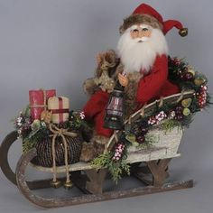 This Lighted Woodland Sled Santa from Karen Didion is perfect for the outdoorsy person. Santa sits in his painted wooden sled, dressed in traditional red    pants, jacket and hat trimmed with brown faux fur. The decorated basket is full of presents and Santa holds a lighted flickering lantern to show the way to    all the homes.                Handpainted face and hands                    Glass inset eyes                    3-ft. cord plugs into a standard outlet                    Desig...