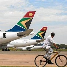 A man cycles past Airbus Group NV left and aircraft operated by South African Airways at OR Tambo International airport in Johannesburg. Jet Airways, Kempton Park, City Press, Africa Destinations, Somewhere In Time, Thing 1, Long Haul, Beach Club, South Africa