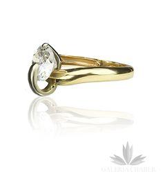 Nowoczesny pierścionek wykonany ze złota próby 585. Obrączka o przekroju koła - kształt oponki o szerokości około 0,3 cm. Na środku osadzono w nietypowy sposób cyrkonię o średnicy około 0,8 cm przytrzymaną kawałkiem białego złota. Całośc prezentuje się nowocześnie.