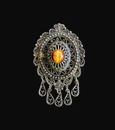 Beautiful and unique pendant/brooch. Can be worn on a chain or as a brooch pin. Tested .925 Sterling Silver And Tigers Eye. Detailed filigree and scroll design. Center and setting is raised to focus on this beautiful stone. Tear drop scroll dangles give this piece movement. In excellent condition.   #victorianbrooch   #victorianpendant   #tigerseyebrooch   #tigereyependant   #sterlingsilverbrooch   #sterlingsilverpendant   #danglebrooch   #danglependant   #giftforher   #shopnow
