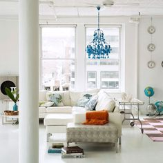 beautiful NY loft. Elements I like here are the specially tinted blue chandelier, the globes and hanging clocks, and the overall clean, open look