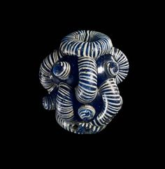 Glass bead, barrel-shaped, blue with white & blue collar either end and two groups of vertical ribs with blue and white bosses between.