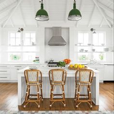 Vintage gymnasium lights were rewired and strung on rope for industrial eclecticism above this island | Coastalliving.com