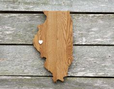 """Illinois State Shape Wood Cutout Sign Wall Art in Oak. 18"""" tall. 6 Stain Colors. Personalized with Choice of Wooden Dimensional Heart or Star at Hometown Location. State Your Love for Illinois with this state shaped wood cutout sign. Handcrafted from repurposed Oak flooring and finished in your choice of 6 stain colors protected by a polyurethane top coat. Shown in Early American stain. ¾"""" deep x 10"""" wide x 18"""" tall at longest points on the shape. Choice of Heart or Star embellishment at..."""