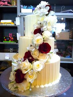 3-tier Wicked Chocolate wedding cake iced in white chocolate ganache, decorated with white chocolate drizzle, red & cream roses & white inca lilies by Charly's Bakery, via Flickr
