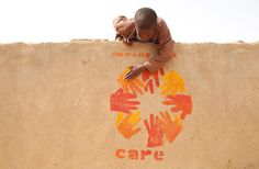A child places his hand within the hands of the CARE logo, painted on a wall next to a borehole drilled and maintained by CARE in Iriba, Chad. In the midst of the food crisis, women and children are spending up to 12 hours a day searching for safe water for their families.