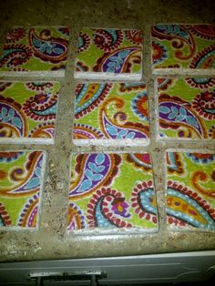 These are mine, and I made them (Holli Maxwell). Super easy to make. You'll need natural stone tiles, mod podge, a paint brush, felt tips (for furniture feet) cocktail napkins, and poly acrylic.  Brush tiles with 1 coat of mod podge. Cut and adhere squares from cocktail napkins to tiles. Brush with an additional coat of Mod Podge and let dry. Brush with 2 coats Poly Acrylic and let dry thoroughly. Once dry, apply felt pads to bottom, and you're done. :) Happy Crafting, kids!  Brush tiles