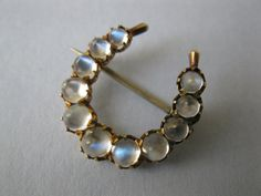 A glowing moonstone horseshoe brooch that is from the Victorian era.