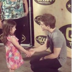 Hunter and a small child. AWWWWWW look at how it looks like hes reeeally into what shes saying and hes crouched down for her! Thats so cute!