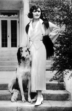 Pola Negri in a gorgeous outfit, a waistcoat and long pleated skirt and strapped shoes with cuban heels. The fur details on the cuff and collar add luxury and elegance to the outfit and the dog is just far too cute.