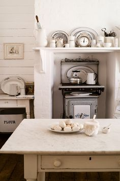 White minimalist traditional kitchen with marble work top, vintage furniture and mantlepiece shelf above old fashioned oven.