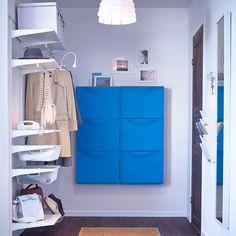 Blauwe schoenenkasten samen met witte wandplanken in de gang