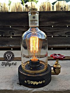 New from Fifty1st is, yep another lamp for your viewing pleasure! Hand crafted reclaimed wood base, brass fittings, water valve switch, vintage cloth cord, reclaimed Rebel Yell whiskey bottle and a whole lot of man sweat! Ever wonder what a creation from Edison would look like if he drank a lot? Well here ya go Lamp Dimensions* Weight: 5lbs Height: 8 inches Width: 4.5 Pipe Fittings: 3/4 brass Valve switch: Brass with red knob Bulb Outlet: 120v/60w max Bulb: Edison style 60 watt...