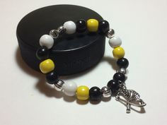 Wear the pride in your favorite hockey player on your wrist with a customized Player Pride Bracelet!  Each beautiful, customized bracelet has your player's number surrounded by beads in your team's colors and either a skater or goalie mask charm!