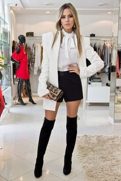 White top with off white jacket and black shorts with black thigh high boots