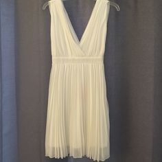 "White Pleated Flowy Dress Size XS New with Tags! White dress with pleating throughout, very flowy. Band at low waist with low V neck. 5'5"" model, lays mid thigh. Pure white. Lined. Moon Collection Dresses Midi"