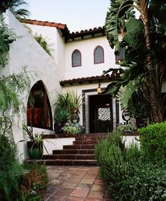 Spanish Style Home. Love the idea of a Courtyard!!  Pale stucco, arched entries and window, and tile roofs with no overhanging eaves define this appealing architecture seen mostly in the western states. You'll often find terra cotta tile underfoot and many Spanish style homes have courtyards in front or back with lush gardening.