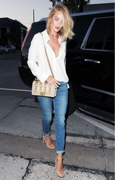 Rosie Huntington-Whiteley wears a white blouse, skinny cuffed jeans, nude sandals, and a Chanel bag